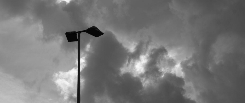 Fotografie Flutlicht unter dunklen Wolken, schwarz weiss