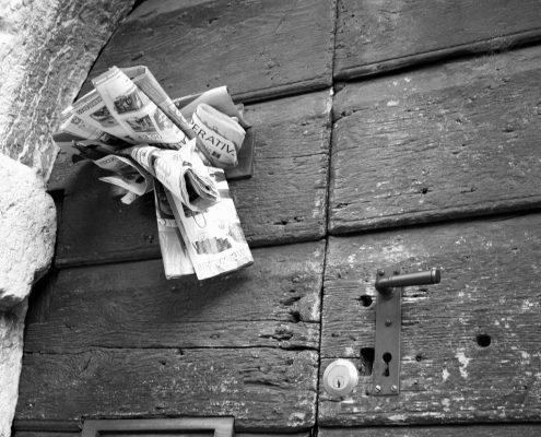 massive alte Holztür mit überfülltem Briefkasten