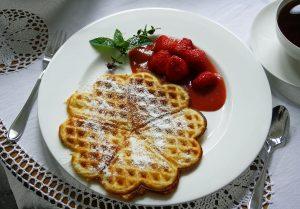Sonntag mit Waffeln, mit Staubzucker, frischen Erdbeeren und Rhabarber-Kuli