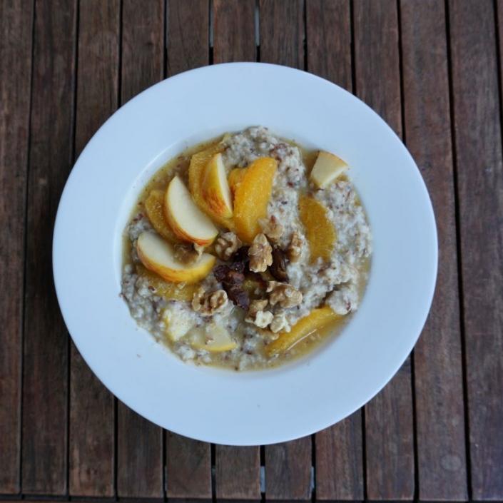 Haferflocken zu Porridge mit Wasser gekocht, dazu Apfel, Orange, Dattel, Kardamon und Nüsse