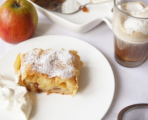 Stückchen Apfelstrudel, gefüllt mit Äpfeln, in Rum eingelegten Rosinen und Mandelstiften, bestäubt mit Puderzucker, dazu einen Rüdesheimer Kaffee, Rezept und Foto von Birgit Puck