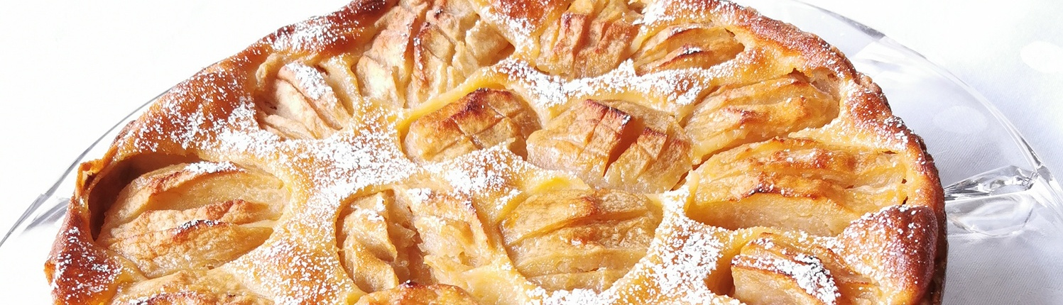 Apfelkuchen aus der Springform gebacken, die Äpfel versunken in einer Eier-Sahne-Mischung mit Puderzucker bestäubt