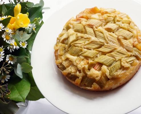 Rhabarberkuchen mit Boden aus Rührteig auf weißem Teller für die Kaffeetafel