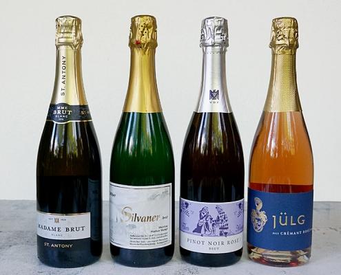 vier Flaschen Sekt brut aufgereiht, Madame Brut von St. Antony, Silvaner Sekt von Stumpf, VDP Pinot Noir Rosé von Minges und Crémant Rosé von Jülg
