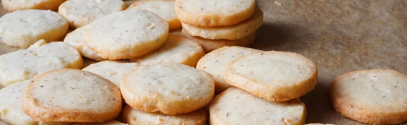 Kekse mit Mandeln, rund, von der Rolle geschnitten, gebackenes Mürbteiggebäck auf Backpapier