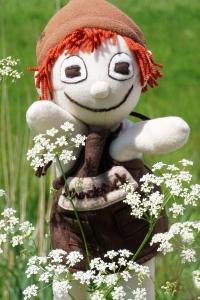Der Schokopuck genießt die Natur. Hier steht die Handpuppe in einem sommerlichen Feld hinter der Schafgarbe.