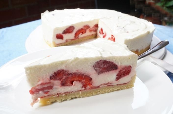 Tortenstück Schmandkuchen mit frischen Erdbeeren auf weißem Teller, im Hintergrund die angeschnittene Erdbeertorte