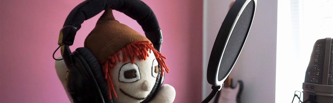 Songs für Kinder nimmt die Handpuppe Schokopuck im Tonstudio auf, hier steht er mit Kopfhörer vor dem Mikrofon