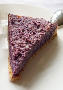 veganer Kuchen ohne Zucker mit Heidelbeeren, Tortenstück auf weißem Teller